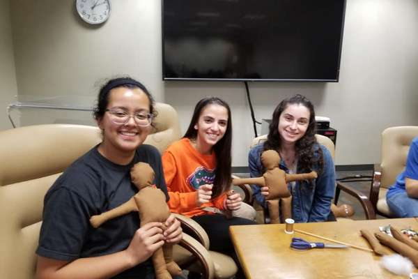 Three students sit behind a table, showing off the dollies they have made